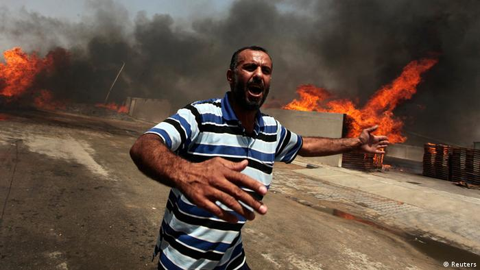 A man yelling as a fire burns after an explosion in the Gaza Strip Photo: REUTERS/Ashraf Amrah