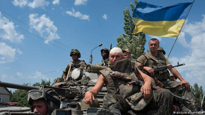 Ukrainian government soldiers drive atop an armored personal carrier with a Ukrainian national flag, outside the city of Siversk, Donetsk region, eastern Ukraine, Saturday July 12, 2014. (AP Photo/Evgeniy Maloletka)