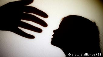 A hand moves toward the silhouette of a child's face