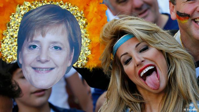 A woman sticking her tongue out, with a picture of Chancellor Merkel next to her (Reuters)