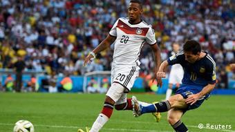 Lance de futebol envolvendo Boateng e Messi em campo