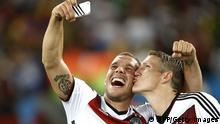 Germany's midfielder Bastian Schweinsteiger (R) and Germany's forward Lukas Podolski (C) take a 'selfie' after their victory in extra-time in the final football match between Germany and Argentina for the FIFA World Cup at The Maracana Stadium in Rio de Janeiro on July 13, 2014. AFP PHOTO / ADRIAN DENNIS (Photo credit should read ADRIAN DENNIS/AFP/Getty Images)