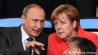 Angela Merkel talks to Russian President Vladimir Putin during the 2014 FIFA World Cup final match (Photo: PEDRO UGARTE/AFP/Getty)