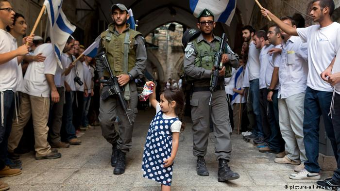 A little girl stands with border police