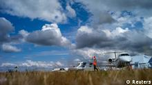 An aircraft marshall directs an aircraft to its parking stand at the 2014 Farnborough International Airshow in Farnborough, southern England July 13, 2014. REUTERS/Kieran Doherty (BRITAIN - Tags: TRANSPORT SOCIETY)