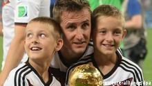 Germany's Miroslav Klose holds the trophy with his sons on the pitch with after winning the FIFA World Cup 2014 final soccer match between Germany and Argentina at the Estadio do Maracana in Rio de Janeiro, Brazil, 13 July 2014. Photo: Andreas Gebert/dpa (RESTRICTIONS APPLY: Editorial Use Only, not used in association with any commercial entity - Images must not be used in any form of alert service or push service of any kind including via mobile alert services, downloads to mobile devices or MMS messaging - Images must appear as cstill images and must not emulate match action video footage - No alteration is made to, and no text or image is superimposed over, any published image which: (a) intentionally obscures or removes a sponsor identification image; or (b) adds or overlays the commercial identification of any third party which is not officially associated with the FIFA World Cup) EDITORIAL USE ONLY