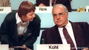 Angela Merkel stands bending down to a seated Helmut Kohl in 1991