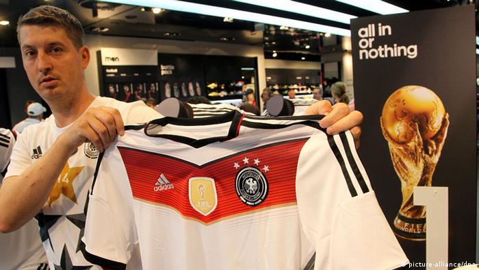 Продавец показывает новую футболку Adidas с четырьмя чемпионскими звездами