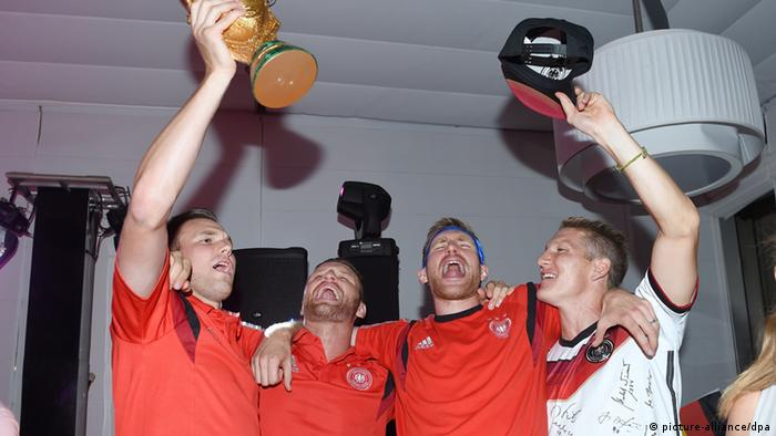 Kevin Großkreutz (l.-r.), Shkodran Mustafi, Per Mertesacker und Bastian Schweinsteiger feiern im Hotel Sheraton in Rio de Janeiro mit dem WM-Pokal (Foto: Markus Gilliar/DFB/dpa)
