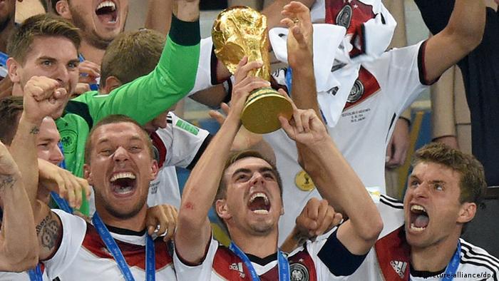 Philipp Lahm (2.v.l.) hebt eingerahmt von Lukas Podolski (l.) und Thomas Müller (r.) den WM-Pokal in den Himmel von Rio de Janeiro (Foto: Marcus Brandt/dpa)