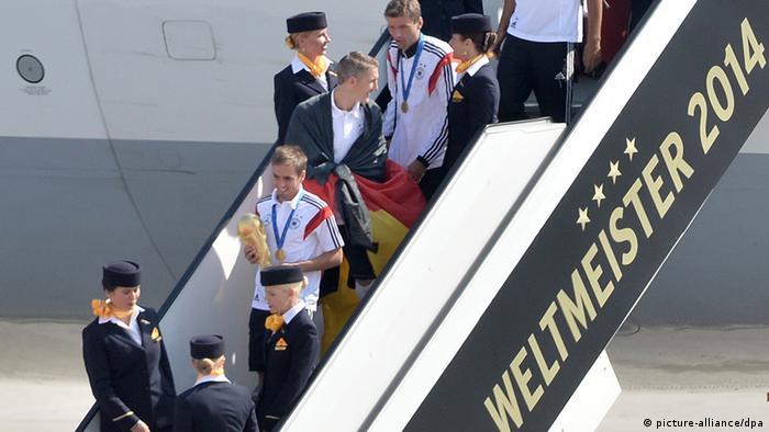 Philipp Lahm steigt nach der Landung als erster aus dem Flugzeug aus - mit dem WM-Pokal in der Hand (Foto: dpa)