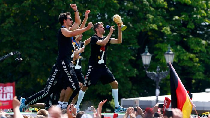 Germany's Thomas Mueller (R) holds the World Cup trophy during celebrations to mark the team's 2014 Brazil World Cup victory (photo: REUTERS/Thomas Peter)