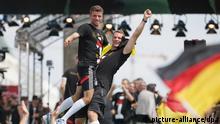 Thomas Müller und Manuel Neuer jubeln am 15.07.2014 beim Empfang der Fußball-Nationalmannschaft in Berlin. Nach 1954, 1974 und 1990 ist Deutschland mit einem Sieg über Argentinien zum vierten Mal Weltmeister geworden. Foto: Michael Kappeler dpa