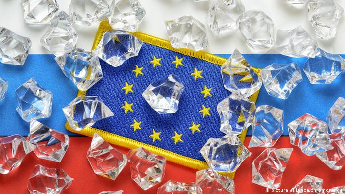 A symbolic image showing Russian and EU flags covered with ice cubes