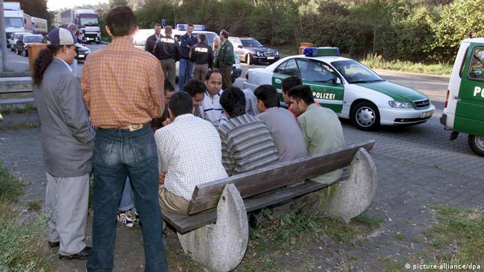 Illegale Einwanderer auf einem Parkplatz unter Polizeibewachung (Foto: dpa)