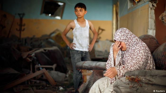 Ein Junge und eine Frau in einem zerstörten Haus im Gazastreifen - Foto: Mohammed Salem