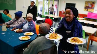 A young girl serves a free meal to elderly people