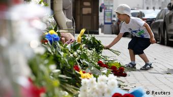 A boy places flowers outside the Dutch embassy in Moscow. (Photo: REUTERS/Sergei Karpukhin)