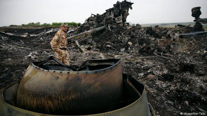 Homem em meio aos destroços incendiados do avião