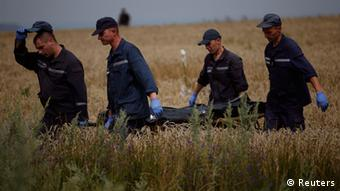 Men carrying a body on a field. (Photo: REUTERS/Maxim Zmeyev)