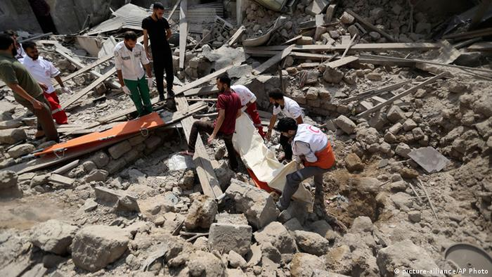 Palestinian medics remove a dead body found under the rubble of a home destroyed by an Israeli strike in the Shajaia neighborhood of Gaza City, northern Gaza Strip, Sunday, July 20, 2014. (AP Photo/Hatem Moussa)