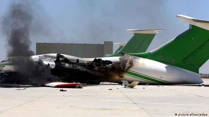 A picture made available on 19 July 2014 shows damaged planes and smoke rises following clashes between rival militias at the main airport of Tripoli, Libya, 16 July 2014. (Photo via EPA/STR)