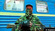 An armed pro-Russian separatist stands guard at a railway station in Donetsk July 21, 2014. REUTERS/Konstantin Cherginsky (UKRAINE - Tags: POLITICS CIVIL UNREST TRANSPORT)