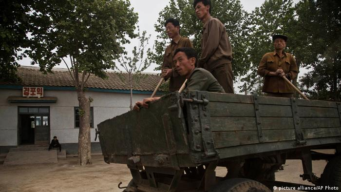 North Korean men ride in a farmer's wagon in North Korea's South Hamgyong province (AP Photo/David Guttenfelder)