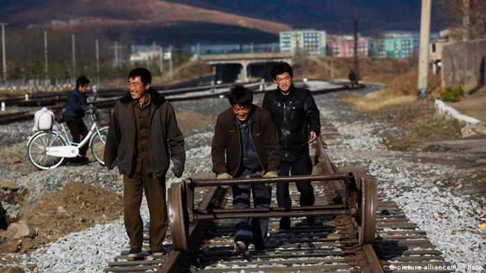North Korean workers push a handcart on a train track (picture alliance/AP Photo)