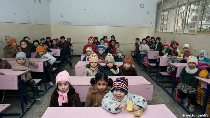 Syrian refugees sit in a classroom