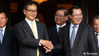 Cambodia's Prime Minister Hun Sen (2nd R) shakes hands with Sam Rainsy (2nd L), president of the Cambodia National Rescue Party (CNRP), after a meeting at the Senate in central Phnom Penh July 22, 2014 (Photo: REUTERS/Stringer)
