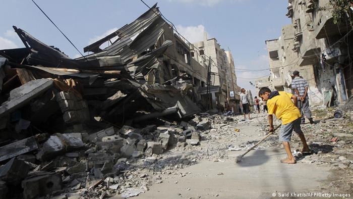 Ein Palästinenserjunge fegt am 22.7.2014 nach einem israelischen Angriff eine Straße in Rafah im Gaza-Streifen (Foto: AFP/Getty Images)