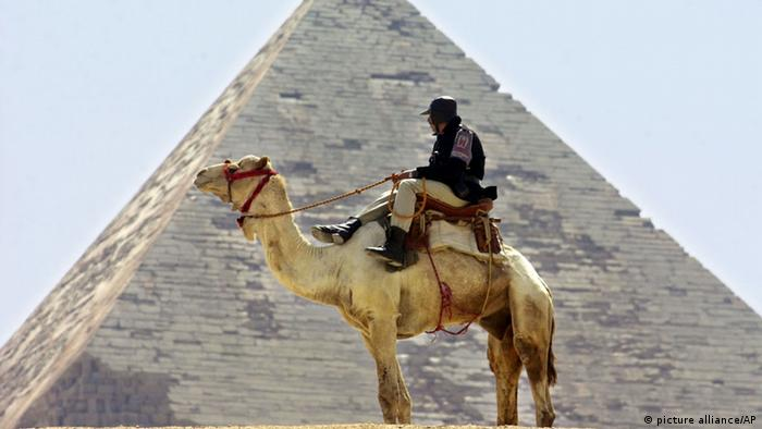 A policeman on a camel in front of the pyramids of Gizeh. (Photo: picture-alliance/ AP)
