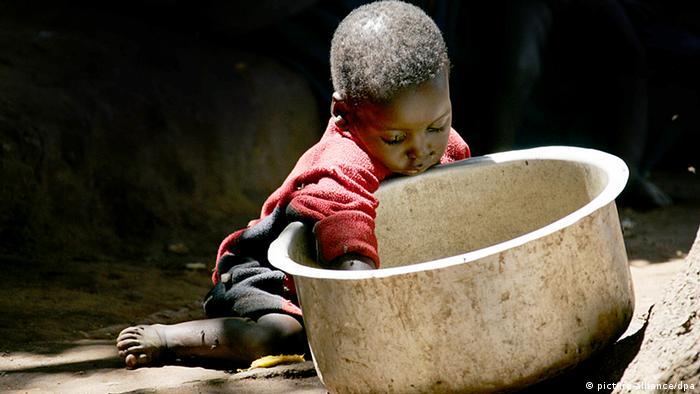 Symbolbild Hungernot in Afrika, Kind sucht in leeren Topf nach Essen