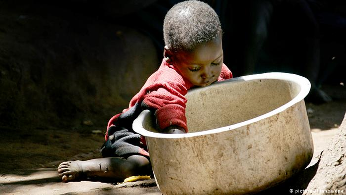 A young boy earing out of a big bowl