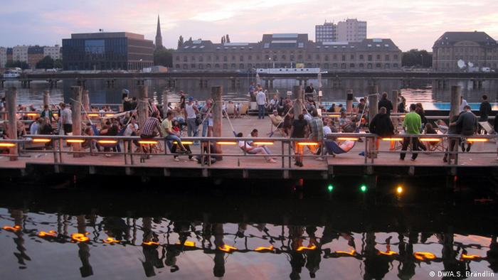 Berlin residents enjoying the sunrise after a night of clubbing at Badeschiff, Copyright: DW / Anne-Sophie Brändlin