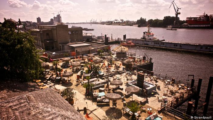 Strandpauli in Hamburg Hafenkräne und die Elbe im Hintergrund. Mit Perspektive von oben das Gelände von Strandpauli mit Liegestühlen und Sonnenschirmen.