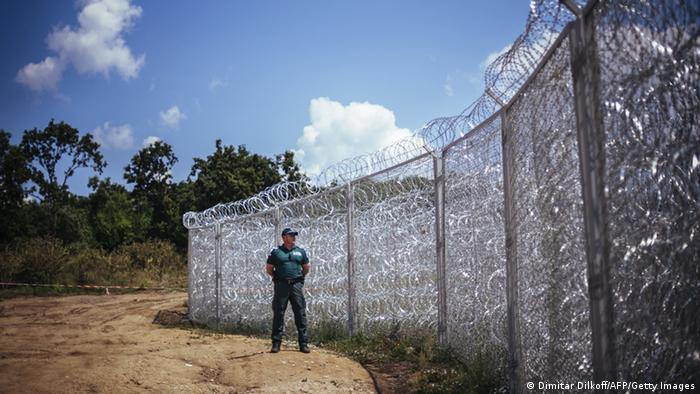 A guard stands watch in front off a barbed wire fence