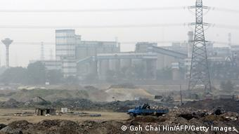 Trucks and bulldozers clear a piece of land for construction of more factories in the suburbs of Beijing 30 June 2005 (Photo: GOH CHAI HIN/AFP/Getty Images)