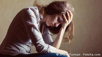 Symbolbild Depression: Eine Frau, die verzweifelt und traurig ihren Kopf mit der linken Hand abstützt.