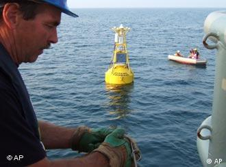 A technician helps install a buoy which will be part of a tsunami warning system developed by GITEWS