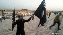 A member of Islamic State waves the group's black flag