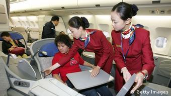 Azafatas chinas con un pasajero de primera clase.  (Foto: China Photos / Getty Images)