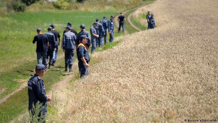 Members of the search and rescue team search the field around the crash site of the Malaysia Airlines flight MH17 near the Grabovo town in Donetsk, Ukraine on July 26, 2014. Soner Kilinc / Anadolu Agency
