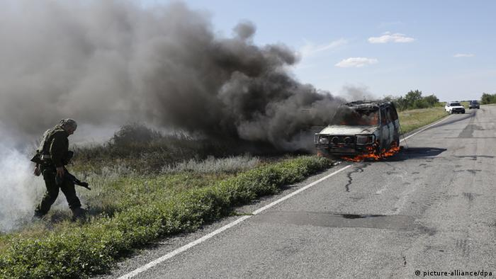 A burning vehicle on the road Lugansk-Krasnodon after an artillery attack by the Ukrainian army. (Photo ITAR-TASS/ Valery Matytsin)