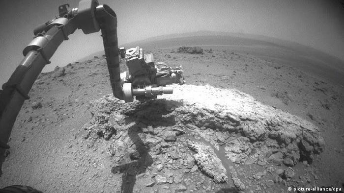 Opportunity untersucht mit seinem Gelenkarm einen Stein (Foto: dpa)