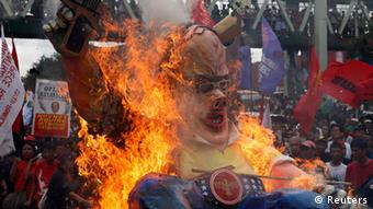 Protesters burn an effigy, made in the satirical likeness of Philippine President Benigno Aquino, as he delivers his fifth State of the Nation Address (SONA) during the joint session of the 16th Congress at the House of Representatives of the Philippines in Quezon city, Metro Manila July 28, 2014.