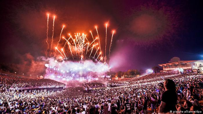 Vast crowds and pink clouds of smoke at tomorrowland music festival