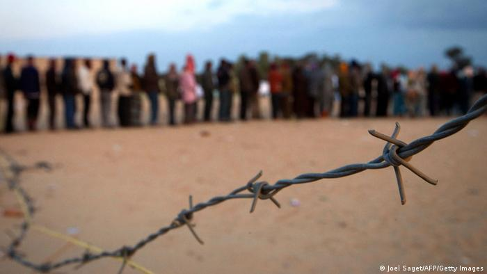 Refugees, who fled from Libya, wait in line behind barb-wire to receive food at the Choucha refugee camp at the Ras Jdir post near the Tunisian border (Joel Saget/AFP/Getty Images)