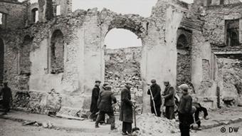 Ruínas de um prédio e pessoas removendo escombros